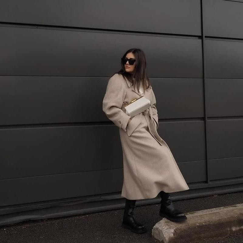 Woman in long jacket standing against wall