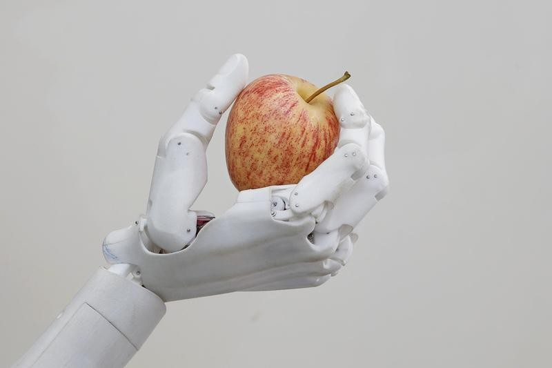 Robot hand holding an apple