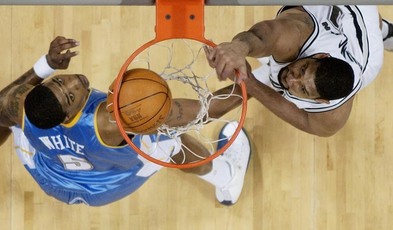 San Antonio Spurs forward Tim Duncan scores over Denver Nuggets defender Rodney White