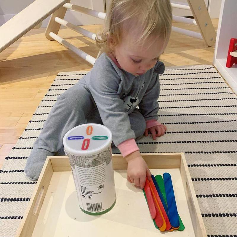 Baby plays with popsicle sticks