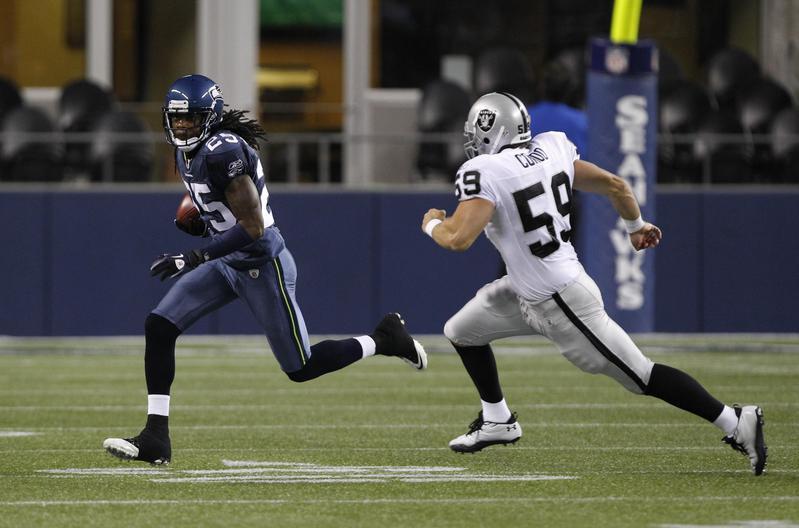 Richard Sherman runs by Jon Condo of Oakland Raiders