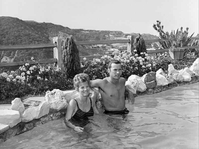Clint Eastwood and his then-wife, Maggie, relax in their swimming pool at their home in Hollywood Hills in 1962.
