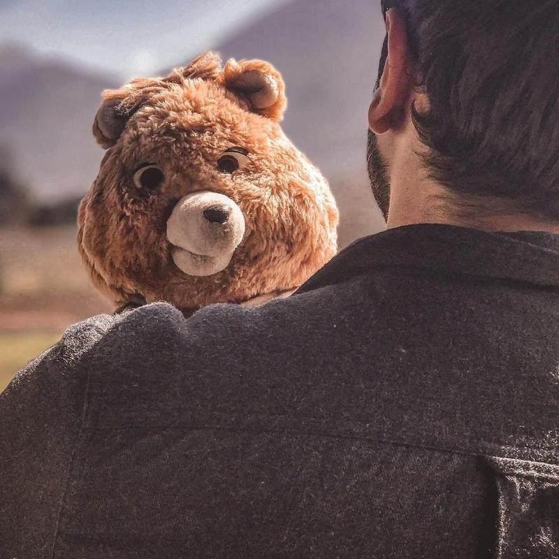 Teddy Ruxpin being held by man