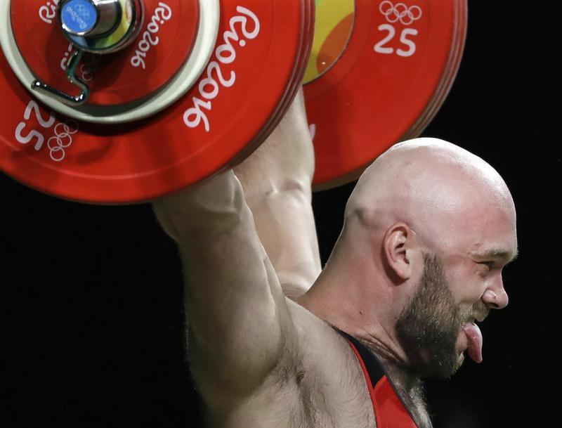 Ruslan Nurudinov sticks tongue out while lifting
