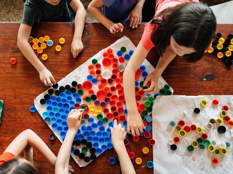 Kids sorting bottle caps