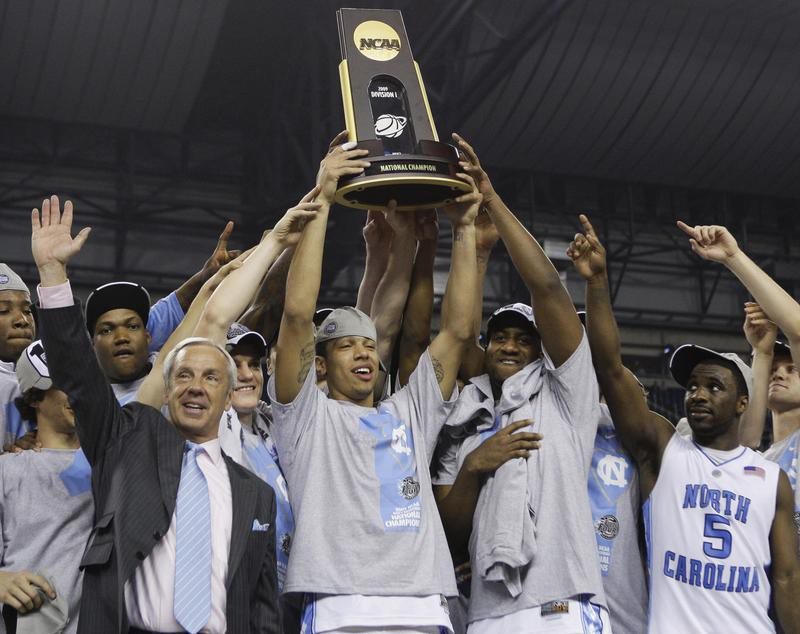 North Carolina coach Roy Williams and players hold up trophy