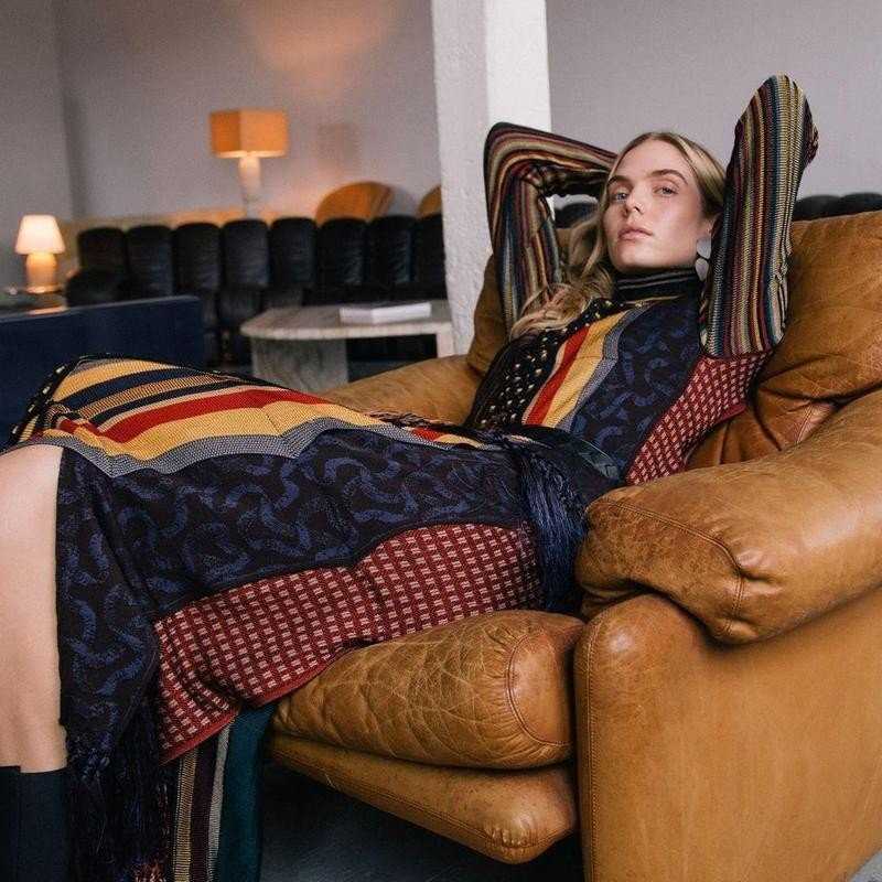 Woman lays on chair in dress