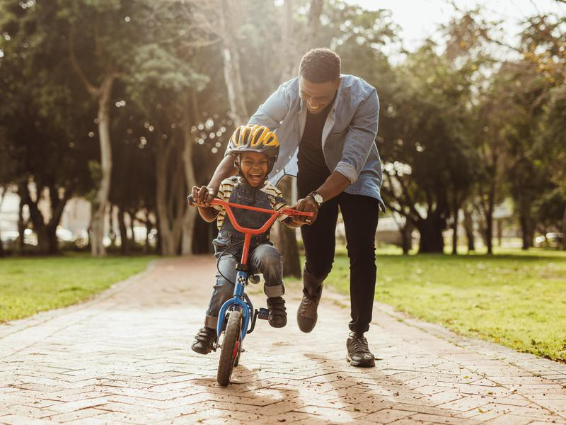 Boy learning to ride a bike with his father