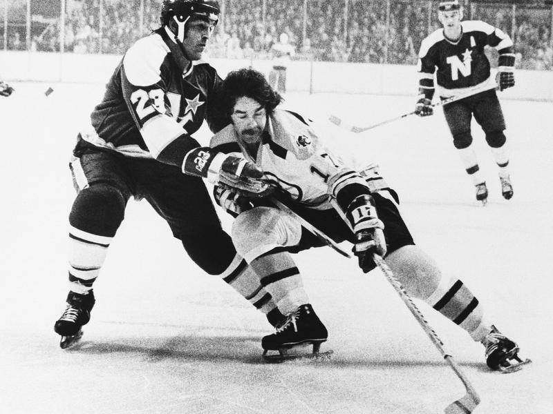 Derek Sanderson and Lou Nanne battle for puck