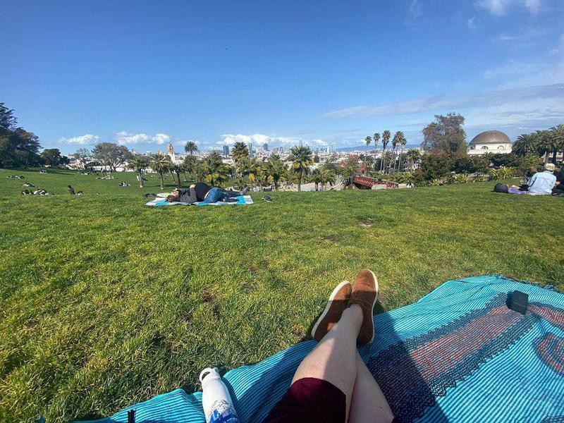 Person sitting on blanket at Dolores Park