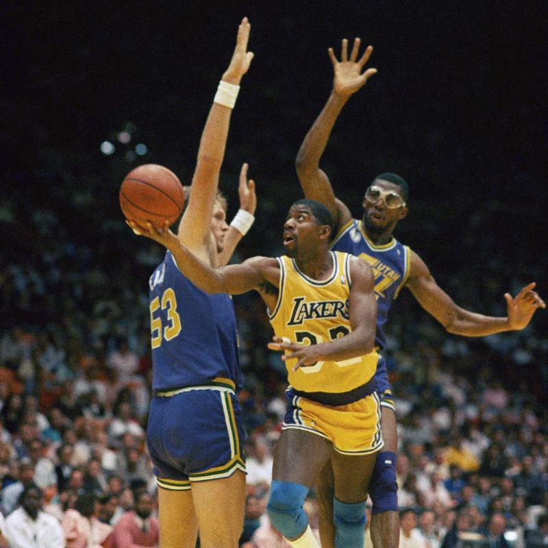 Magic Johnson drives between Utah Jazz players