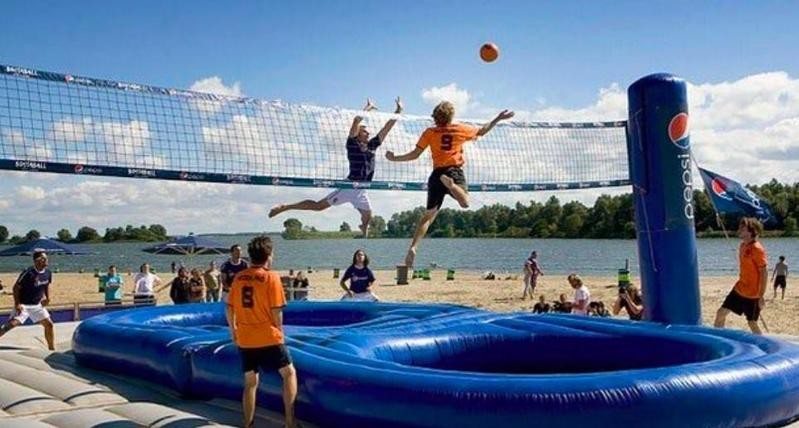 People playing bossaball by the water