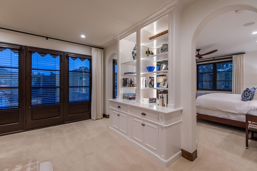 Master bedroom with built-in bookshelf dividing wall