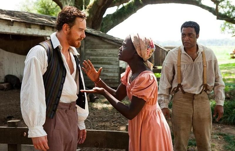Lupita Nyong'o speaking to Michael Fassbender with Chiwetel Ejiofor looking on in 12 Years a Slave