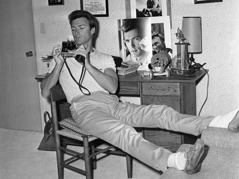 Clint Eastwood, at home in 1965, studies his new camera.