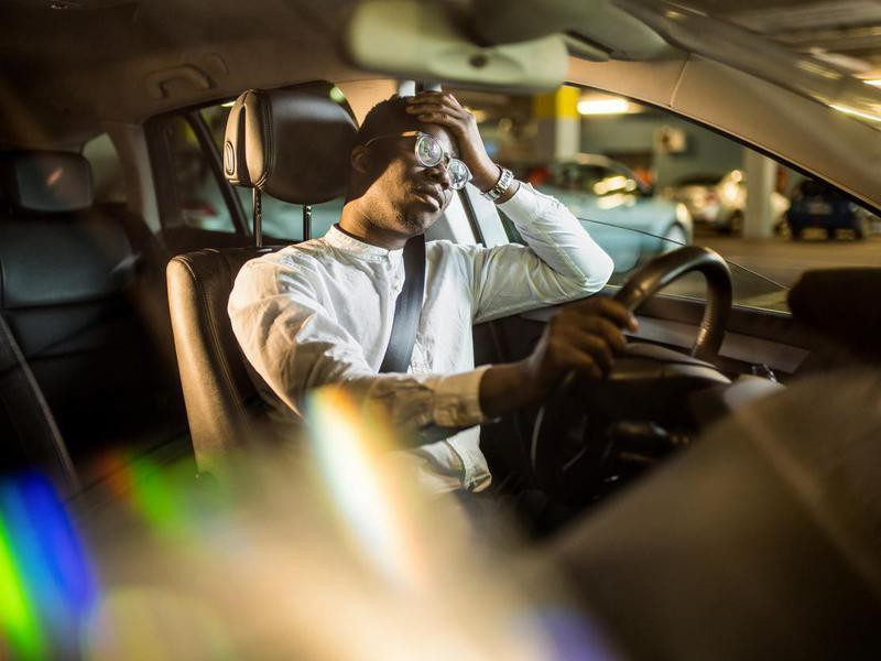Exhausted businessman driving a car