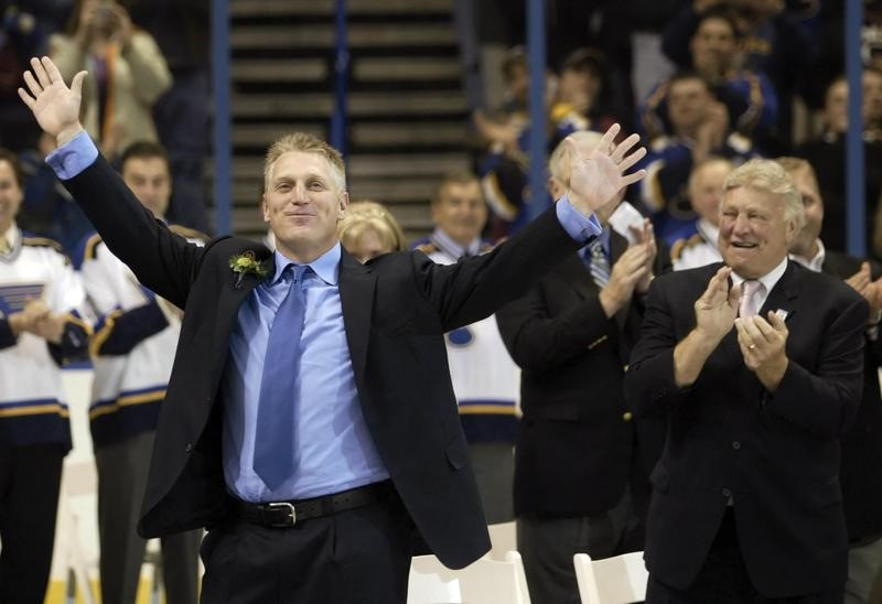Brett Hull waves to fans as father Bobby Hull applauds