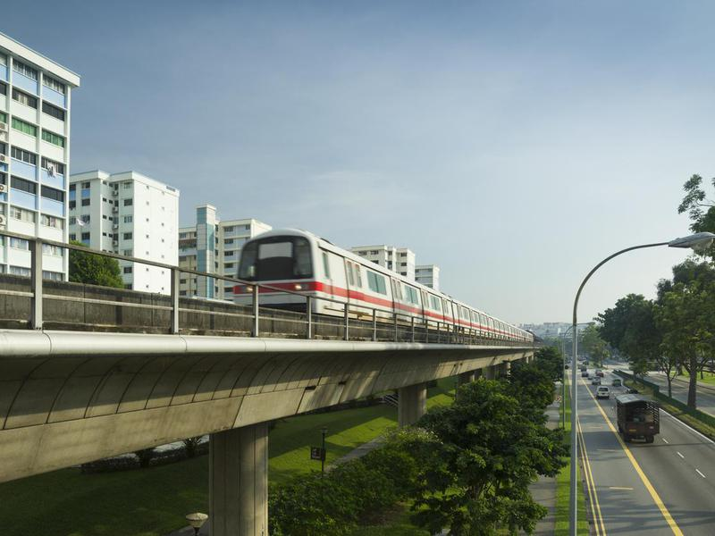 The MRT train on overpass tracks next to buildings and road