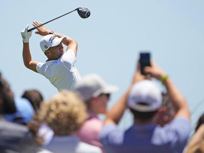 Justin Thomas watches his shot on the ninth tee