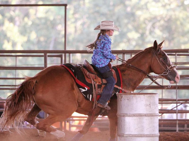 Little Girl running barrels with quarter horse