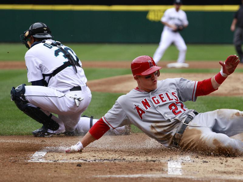 Seattle Mariners catcher Miguel Olivo waits for ball as Los Angeles Angels' Mike Trout scores