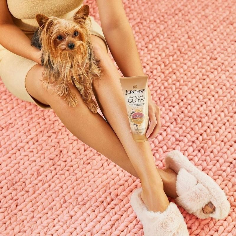Woman posing with dog and Jergens Natural Glow Daily Moisturizer