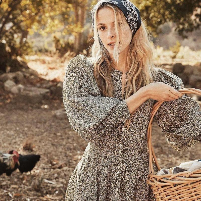 Woman wearing dress in field with basket