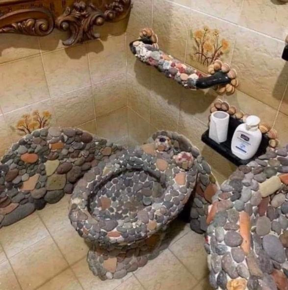 Stone toilet, sink, and decor in bathroom