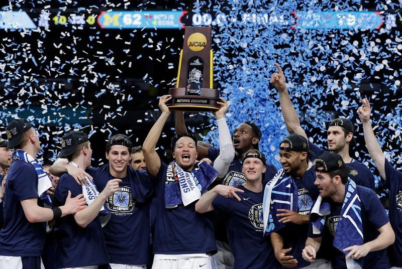 Villanova players celebrate with the trophy after beating Michigan