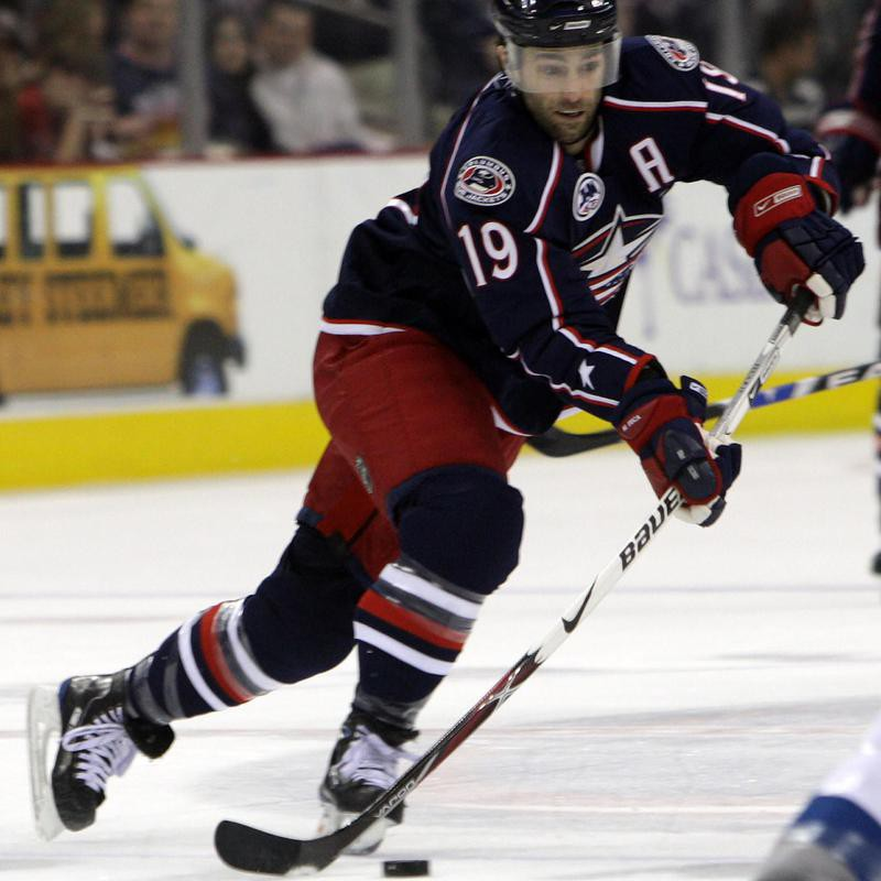 Michael Peca moves puck during game