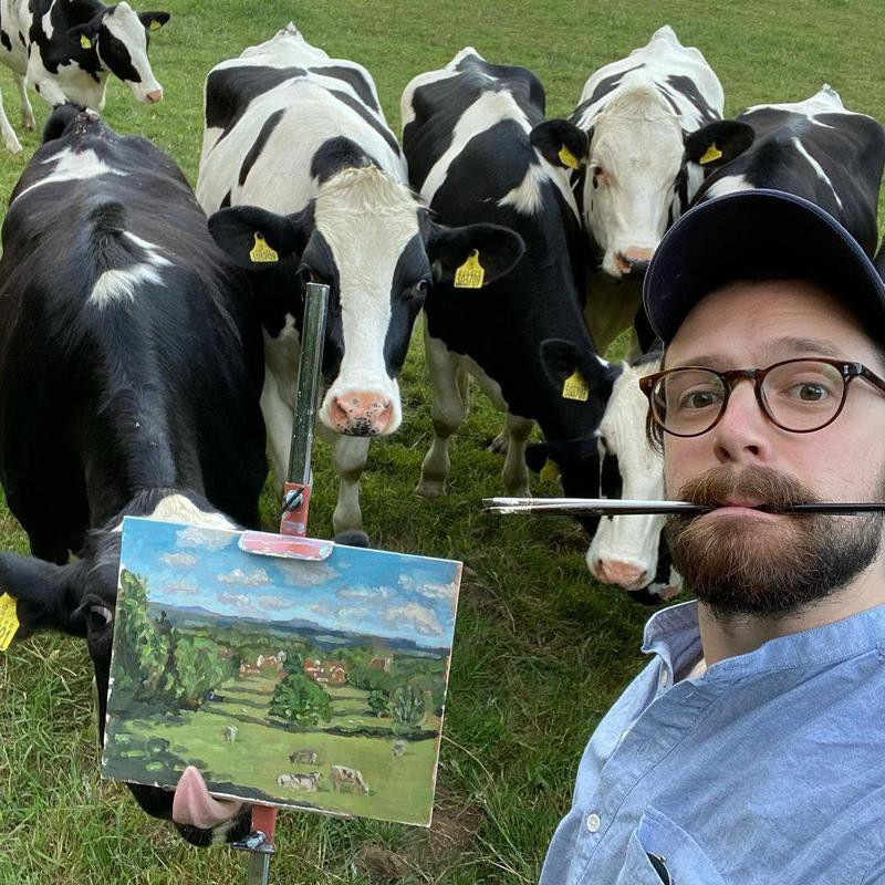 Cows photobombing man painting them