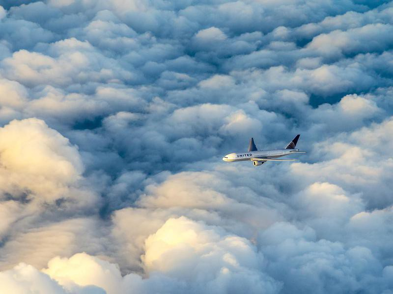 United Airlines aircraft flying over clouds