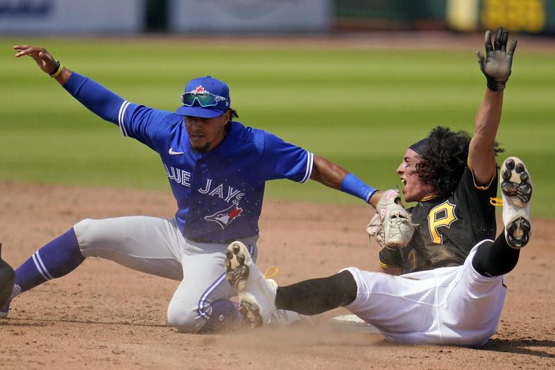 Blue Jays second baseman Santiago Espinal and Pittsburgh Pirates shortstop Cole Tucker slides into second