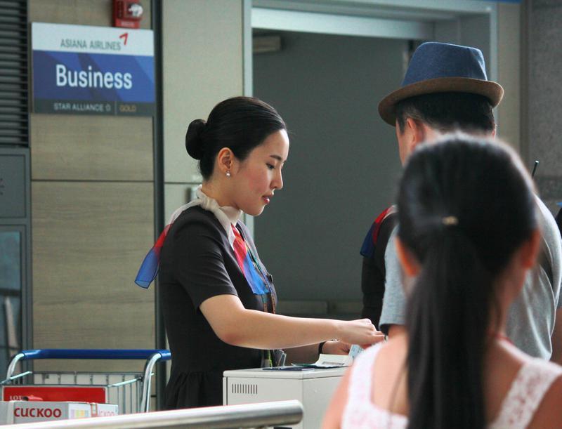 Asiana Airlines flight attendant checks in passengers for boarding