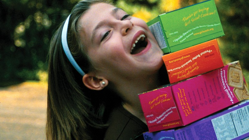 Girl Scout with cookie boxes