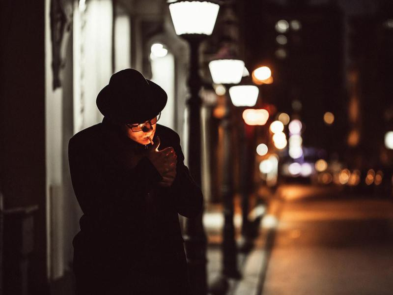man with hat lighting cigarette on city street