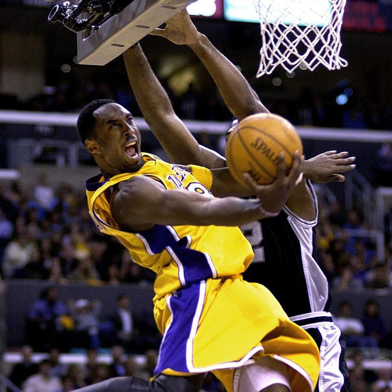 The Los Angeles Lakers' Kobe Bryant swoops under basket and past San Antonio Spurs defender Mark Bryant to score
