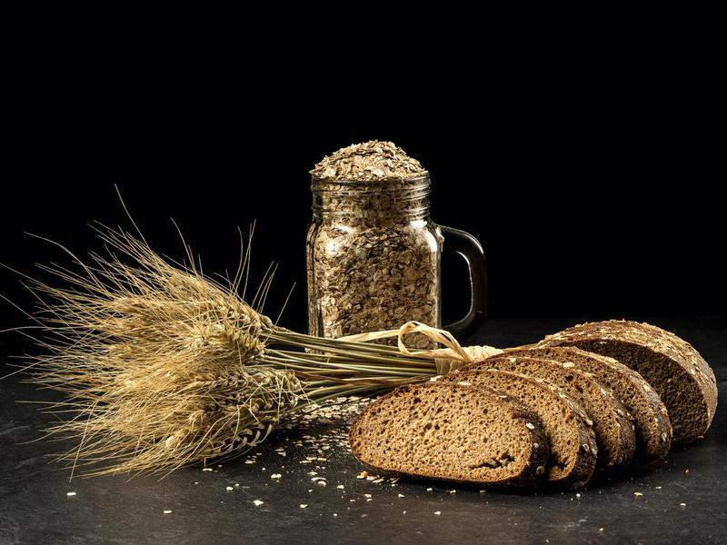 Grain bouquet, golden oats spikelets in jar on dark wooden table, buns and can filled with dried grains.
