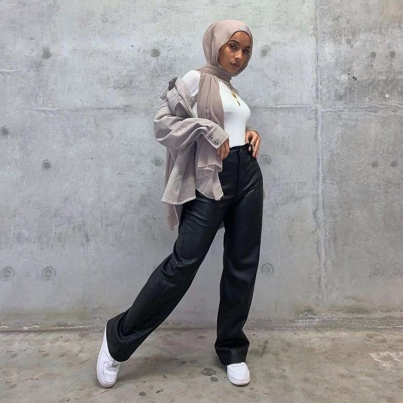 Woman poses in black trousers by wall