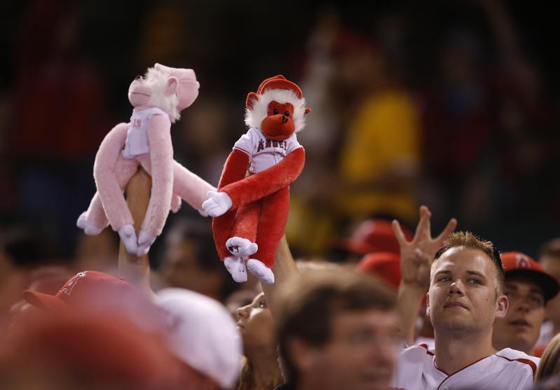 Fans hold up Rally Monkey dolls