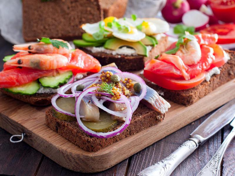 Open sandwich with salted herring, cucumber, red onion, mustard on rye bread