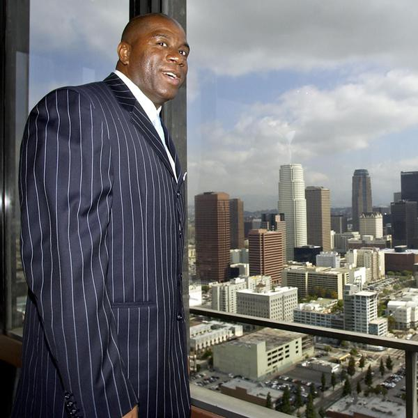FILE - This April 23, 2003 file photo shows former Lakers star Magic Johnson showing the view of downtown Los Angeles from the top floor of the 32-story Transamerica Center, in Los Angeles. A person familiar with the situation says Magic Johnson is part of a group buying the Los Angeles Sparks of the WNBA. The person spoke to The Associated Press on condition of anonymity because no official announcement has been made. The WNBA will officially announce the new ownership at a press conference on Wednesday Feb. 5, 2014 outside the Staples Center. (AP Photo/Nick Ut, File)