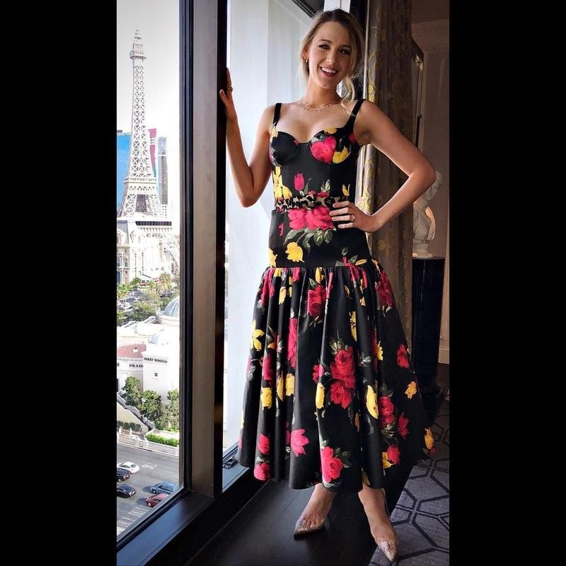 Blake Lively wearing a floral dress by the window