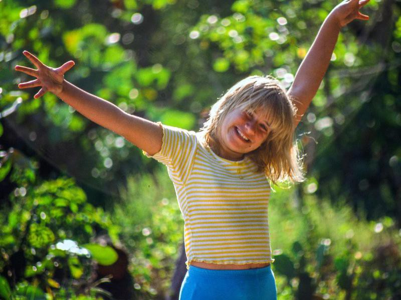 Young girl smiling with her arms outstretched