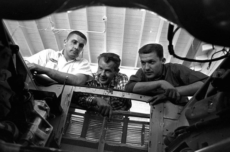Lee Petty looks into engine well with sons Richard and Maurice