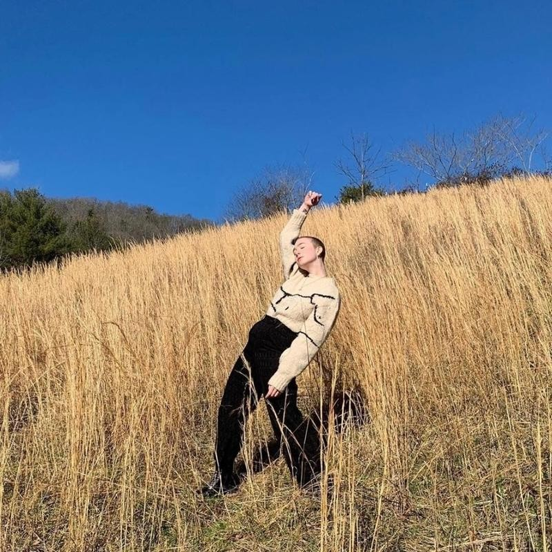 Person poses with arm raised in the weeds