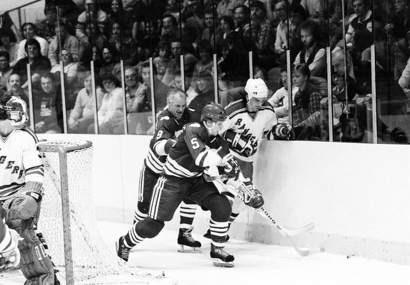 Mark Howe with father Gordie Howe steal puck away from New York Rangers