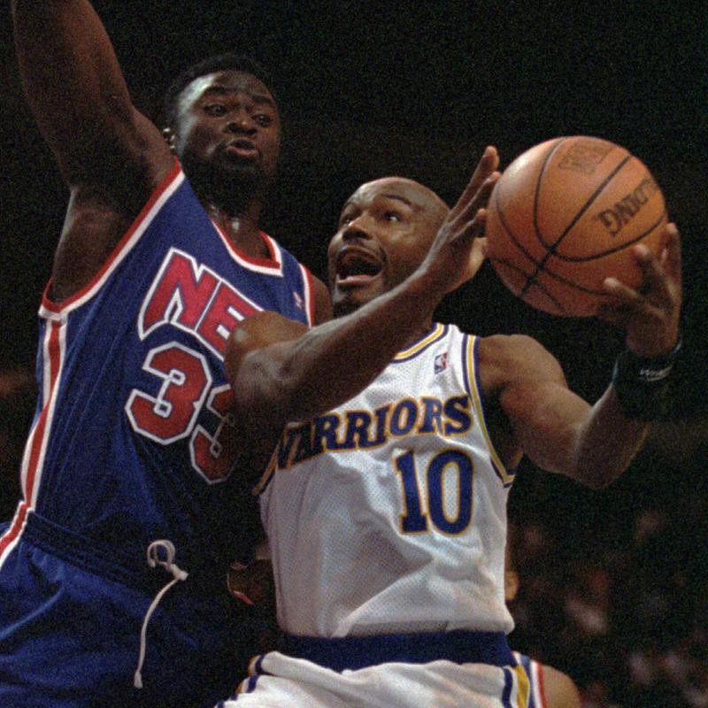 Golden State Warriors' Tim Hardaway goes up for basket as New Jersey Nets' Yinka Dare guards