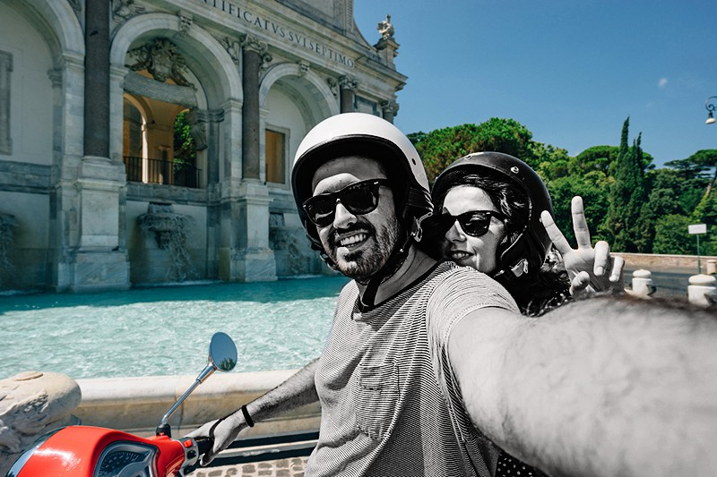 Young adult couple is taking a selfie on a scooter