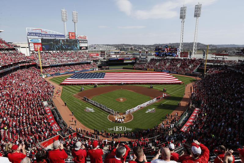 Spectators stand for the national anthem before Opening Day